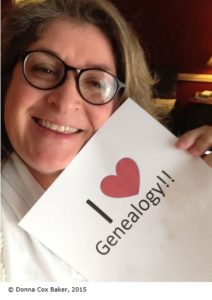 "Donna Baker holds up a sign that says ""I [heart] genealogy."""